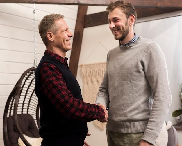 Vista laterale del padre e del figlio si stringono la mano