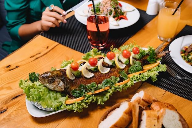 Vista laterale del pane al pomodoro del limone della lattuga di pesce arrostita