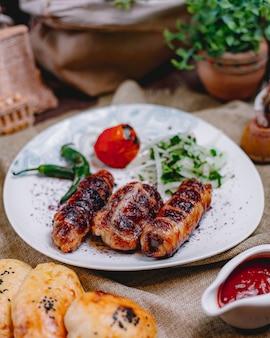 Vista laterale del pepe di verdi di cipolla del pomodoro di kebab del rotolo di pollo