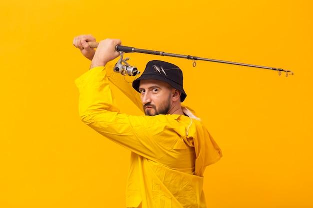 Vista laterale del pescatore che sostiene canna da pesca