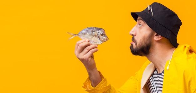Vista laterale del pesce della tenuta del pescatore con lo spazio della copia