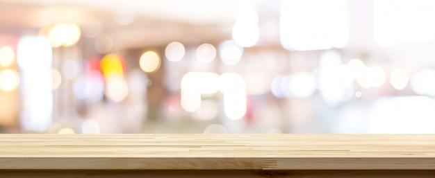 Vista laterale del piano d'appoggio di legno naturale del modello contro il fondo vago del bokeh