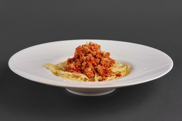 Vista laterale del piatto con spaghetti con carne macinata fritta