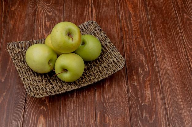 Vista laterale del piatto verde della merce nel carrello delle mele su superficie di legno con lo spazio della copia