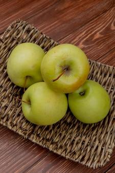 Vista laterale del piatto verde della merce nel carrello delle mele su superficie di legno