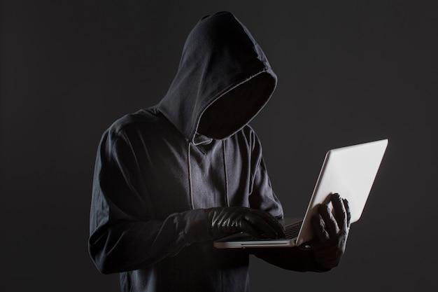 Vista laterale del pirata informatico maschio con i guanti e il computer portatile