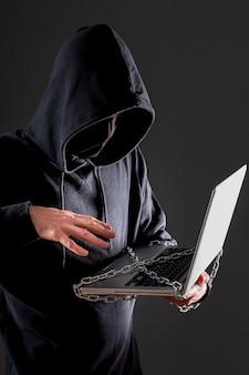 Vista laterale del pirata informatico maschio con il computer portatile protetto dalla catena del metallo
