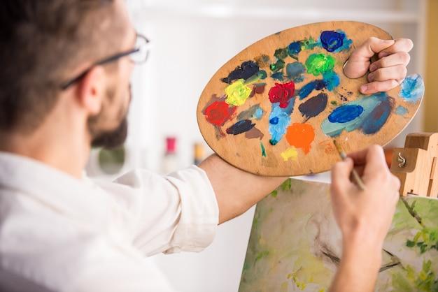 Vista laterale del pittore di grande talento mentre dipinge.