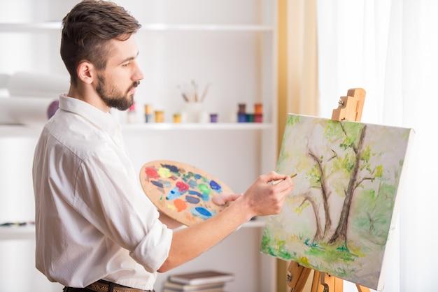 Vista laterale del pittore di talento mentre dipinge la sua foto