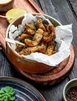 Vista laterale del pollo impanato con le erbe in una ciotola con la salsa di crema e del limone sul bordo di legno su rustico