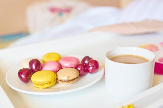 Vista laterale del primo piano della tazza di caffè con gustosi macarons colorati o amaretti