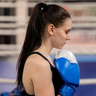 Vista laterale del pugile femmina con guanti protettivi