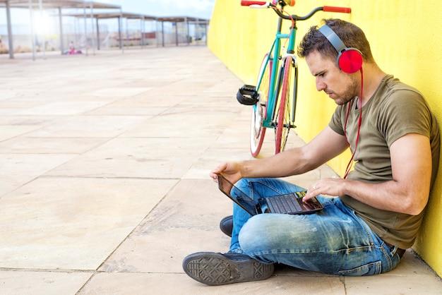 Vista laterale del ragazzo attraente è seduto sul pavimento