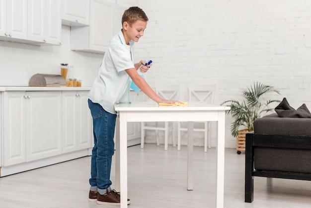 Vista laterale del ragazzo che pulisce la tavola