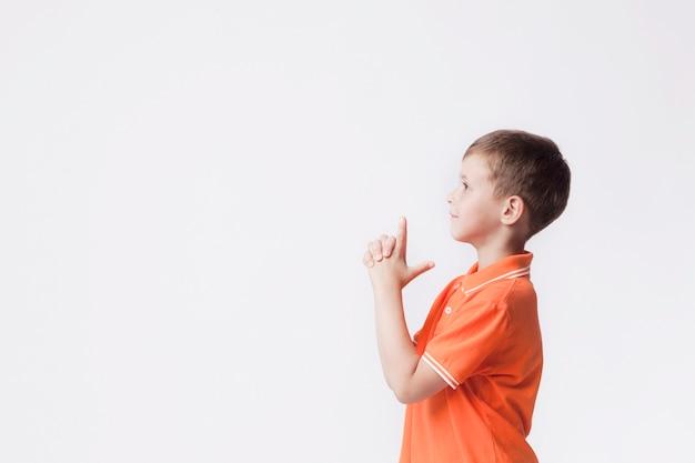 Vista laterale del ragazzo con il gesto della pistola che gioca contro il fondo bianco