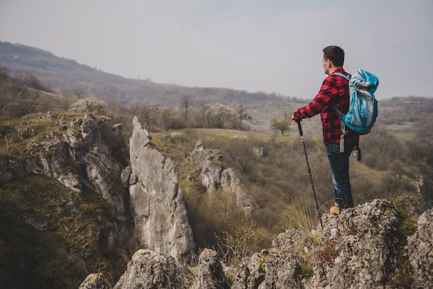 Vista laterale del rambler con lo zaino che gode della natura