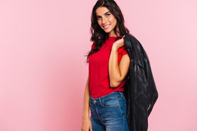 Vista laterale del rivestimento sorridente della tenuta della donna del brunette sulla spalla e sull'esame della macchina fotografica sopra il colore rosa