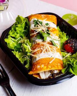 Vista laterale del rotolo del pancake con le verdure e il formaggio del pollo su lattuga in scatola di consegna