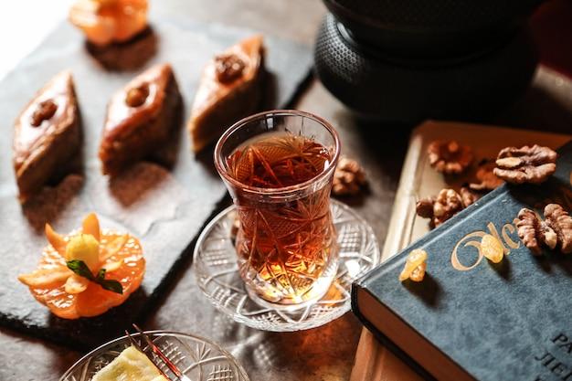 Vista laterale del tè in un bicchiere armudu con baklava e un libro sul tavolo