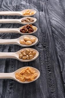 Vista laterale del tipo differente di spuntini come dadi e cracker sui cucchiai di legno con lo spazio della copia sul verticale della superficie di buio