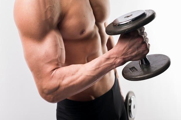 Vista laterale del torso atletico dell'uomo che tiene i pesi
