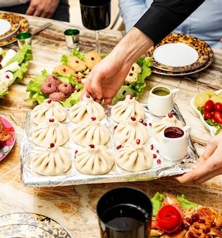 Vista laterale del tradizionale khinkali georgiano servito con salse piccanti salse sul vassoio