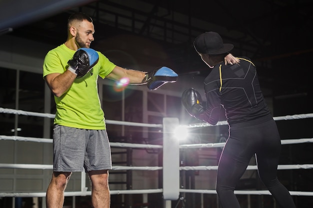 Vista laterale del trainer e boxer femmina sul ring