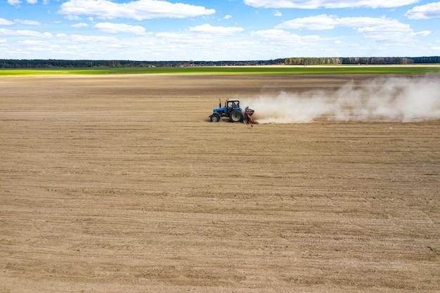Vista laterale del trattore che pianta il seme nel campo, vista aerea del cereale