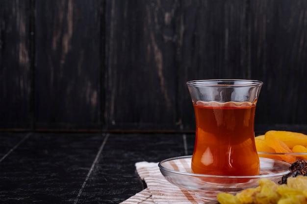 Vista laterale del vetro di armudu di tè con i frutti secchi su fondo rustico nero