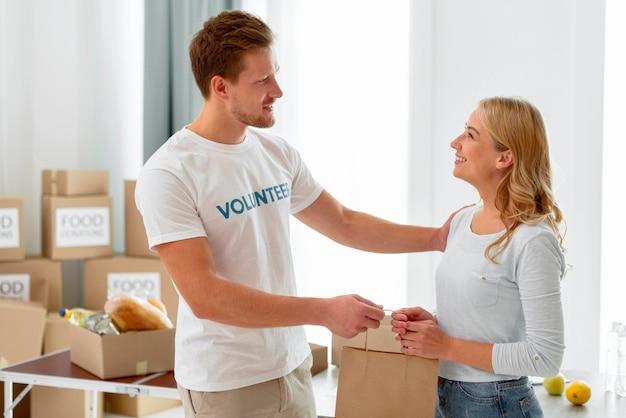 Vista laterale del volontario che distribuisce cibo come donazione
