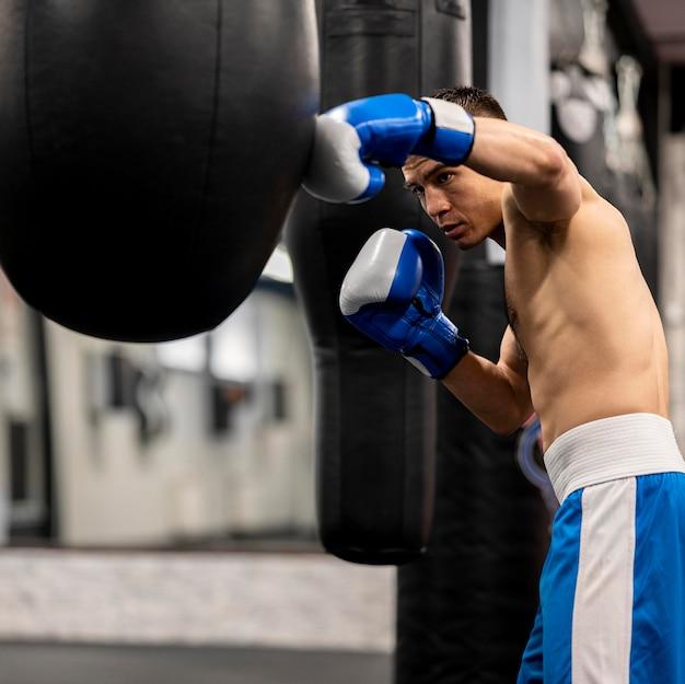 Vista laterale dell'addestramento maschio senza camicia del pugile