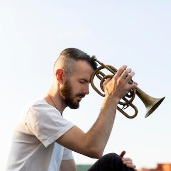 Vista laterale dell'artista maschio con cornetta e copia spazio