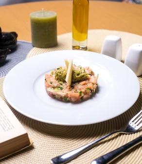 Vista laterale dell'avocado schiacciata salmone mela del cetriolo dell'insalata di pesce