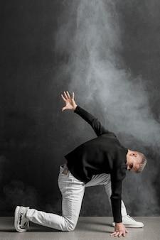Vista laterale dell'esecutore maschio che posa in jeans con fumo