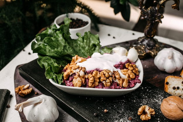 Vista laterale dell'insalata di barbabietola con le noci e la panna acida su un bordo di legno