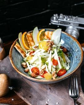 Vista laterale dell'insalata di caesar con pollo e parmigiano in una ciotola su oscurità