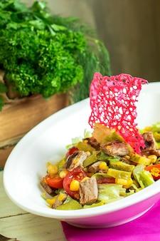 Vista laterale dell'insalata di carne di manzo con verdure tritate e sottaceti in una ciotola
