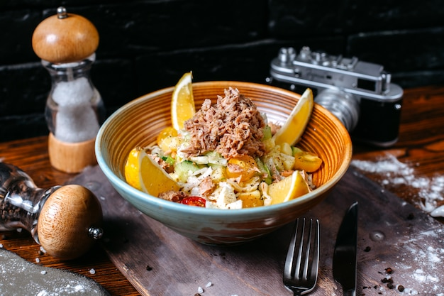 Vista laterale dell'insalata di tonno servita con pomodorini e limone in ciotola