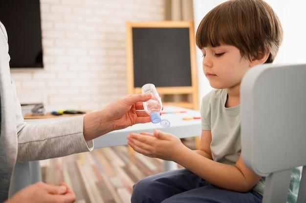 Vista laterale dell'insegnante che dà disinfettante per le mani al bambino prima della lezione