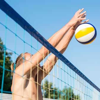 Vista laterale dell'uomo a torso nudo sopra la rete giocando a beach volley