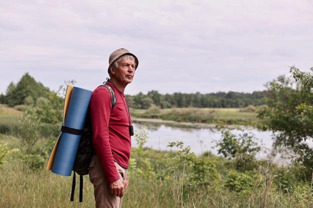 Vista laterale dell'uomo anziano con zaino e tappeto blu, godendo di ammirare la maestosa vista sul fiume mentre si cammina nella meravigliosa campagna durante la sua vacanza attiva. concetto di viaggio e zaino in spalla.