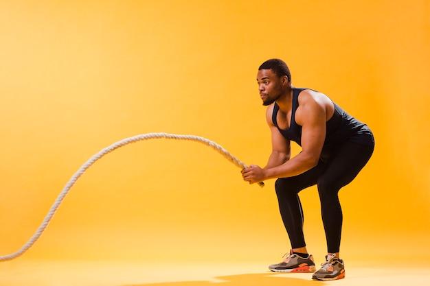 Vista laterale dell'uomo atletico che esercita corda
