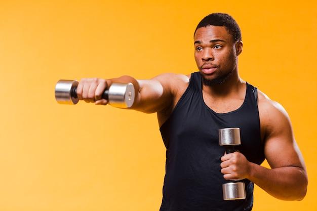 Vista laterale dell'uomo atletico che si esercita con i pesi