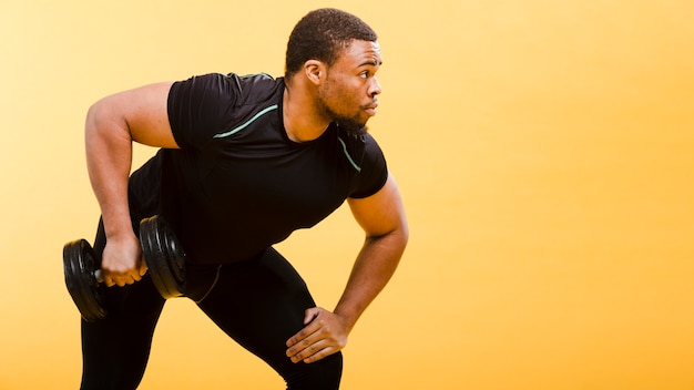 Vista laterale dell'uomo atletico che tiene i pesi