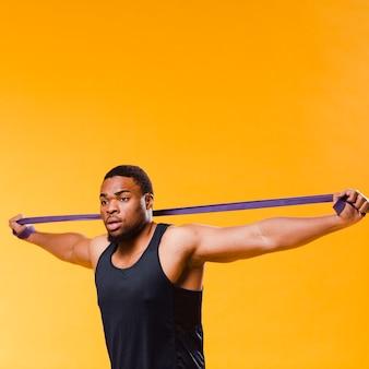 Vista laterale dell'uomo atletico che tira la fascia di resistenza