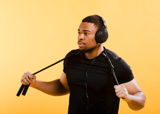 Vista laterale dell'uomo atletico con le cuffie e la corda di salto