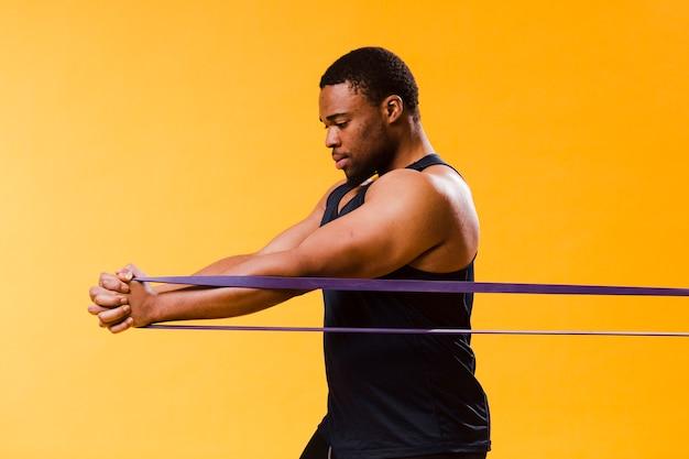Vista laterale dell'uomo atletico in attrezzatura della palestra che si esercita con la banda di resistenza