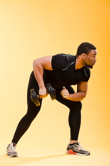 Vista laterale dell'uomo atletico in attrezzatura della palestra che tiene i pesi