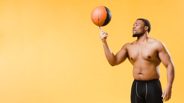 Vista laterale dell'uomo atletico senza camicia con pallacanestro