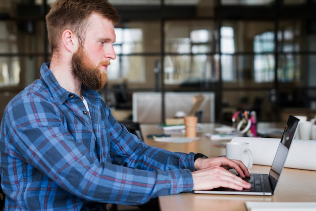 Vista laterale dell'uomo barbuto che porta camicia a quadretti blu facendo uso del computer portatile